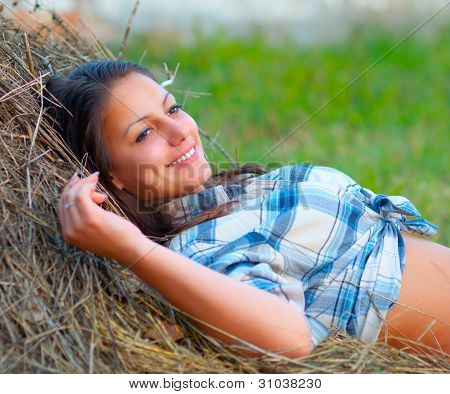 Beautiful young women lies on the pile of hay and smiles