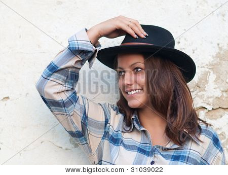 Beautiful cowgirl smiles while holding her hat and leaning on the old wall