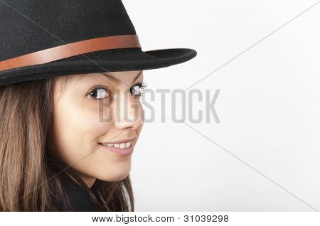 Portrait of the beautiful smiling teenage girl wearing black cowboy hat