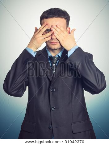 Young Businessman Looking Through His Fingers