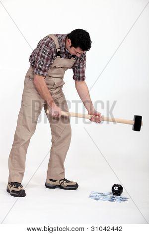 portrait of journeyman breaking money box with hammer