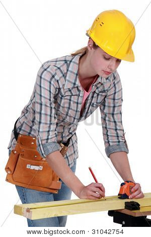 A female carpenter taking measures.