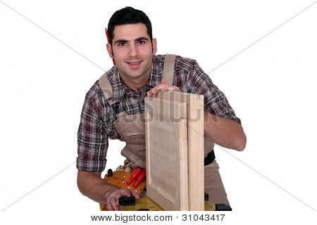 A carpenter working on a closet door.