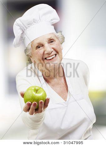 cozinheiro sênior mulher oferecendo uma maçã verde, interior
