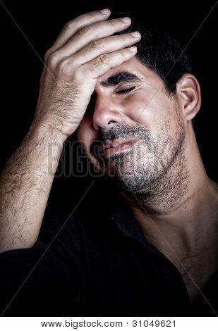 Portrait  of a stressed and desperate young man suffering a strong headache on a black background