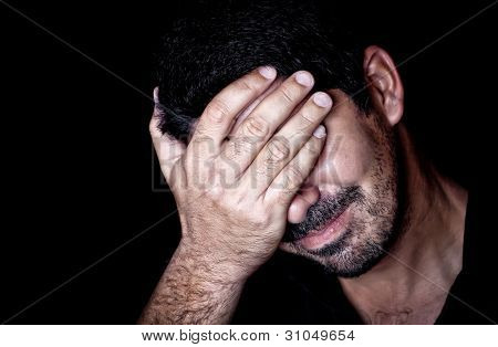 Portrait  of a very stressed young man suffering a headache and covering his face on a black background