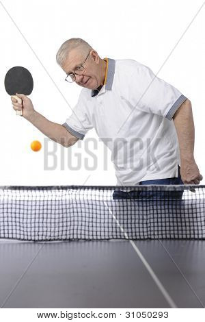 A senior man focused on an approaching ping pong ball as he prepares to hit it back across the net.  Motion blur on ball.  Space on table for your text.  On a white background.