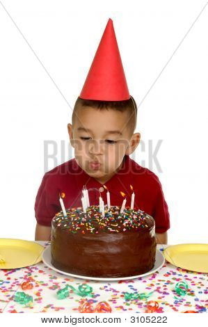 Boy Blowing Out Candles On Birthday Cake