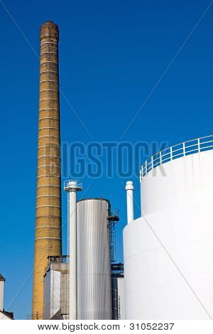 Smokestack and white industrial tank