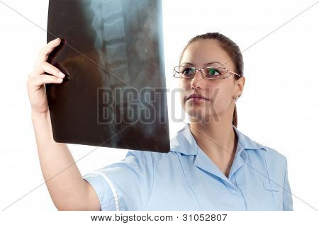 Young female doctor looking at x-ray picture of patients spine