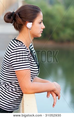 Young attractive girl listens to music while standing on the bridge