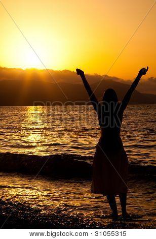 Joven delgada está disfrutando de la libertad. Puesta de sol y mar