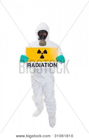 A man in a  hazmat suit holding a sign