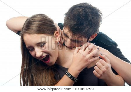 Vampire teenage boy biting neck of the frightened teenage girl that tries to defend herself.