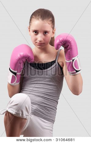 Portrait of pretty kick boxing girl with pink gloves exercising