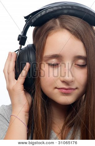 Beautiful teenage girl with closed eyes listens to music through the headphones
