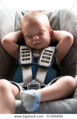 Infant boy sleeps peacefully secured with seat belts while in the car