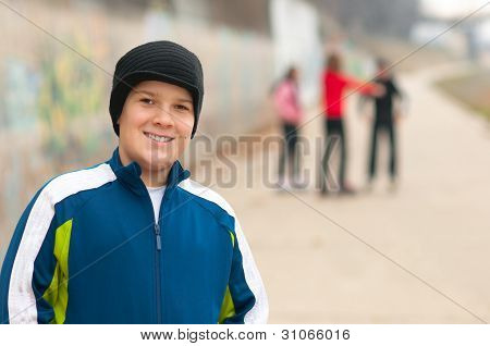 Cute chubby teenage boy having fun with friends on the street