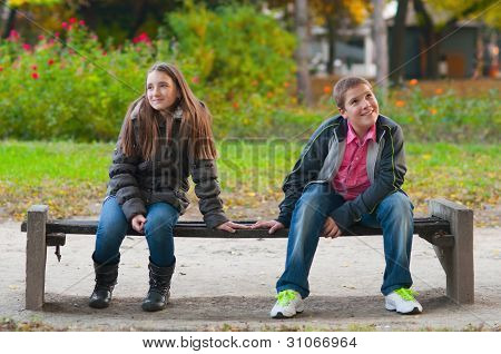 Shy boy and the girl sitting in the park and lightly touching each other finger tips