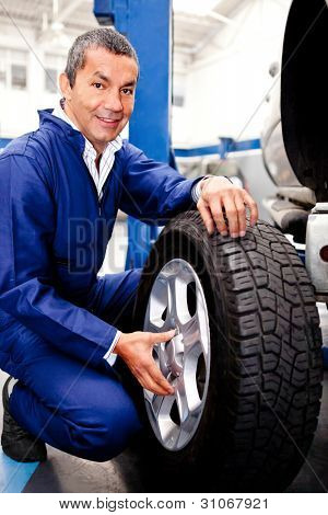 Mechanic fixing a car puncture holding a wheel