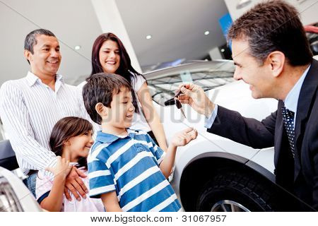 Family buying a new car and getting the keys from salesman