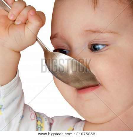 Baby girl holding spoon in mouth. Isolated on white