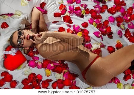 Woman lieing in bed covered by Flower Petals with chocolate candy shaped like a heart