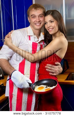 gut aussehend Mann Braten Eier für seine Freundin in der Küche