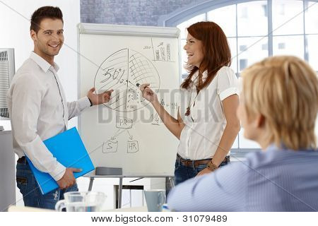 Happy businesspeople working with whiteboard, doing presentation, using diagram.