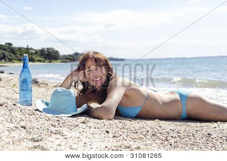 Happy smiling mature woman laying on beach.