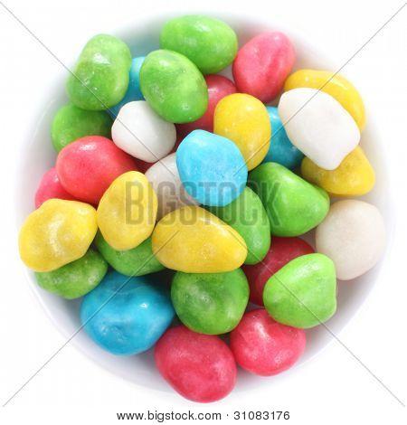 Caramelos multicolores en un plato poco poco planos, aislado en blanco