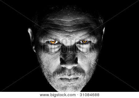 Low Key Portrait Of Menacing Looking Caucasian Man With Orange Bird Eyes