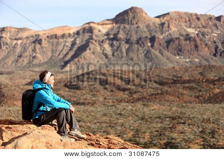 Hiking - woman hiker enjoying view. Woman sitting looking over beautiful volcano mountain landscape. From volcano Teide, Tenerife, Canary Islands, Spain.