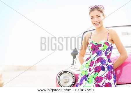 Car woman smiling happy standing in front of pink retro vintage car. Portrait of pretty girl in summer dress.  Multicultural Chinese Asian / Caucasian female lifestyle model. Photo from Havana, Cuba.