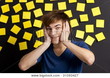 Young student with a funny expression in front of a board full of yellow notes