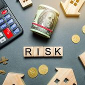 Wooden Houses, A Calculator, Keys, Coins And Blocks With The Word Risk. The Risks Of Investing In Re poster