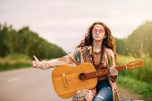 Beautiful hippie girl is standing on a highway and catching a passing car. Spirit of freedom. Fashio poster