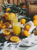 Orange Harvest Concept. Table With Orange Juice And Box Of Oranges And Orange Tree Leaves poster