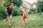 Kids Friends Boy Girl Splashing With Gardening Hose Sprinkler On Backyard On Summer Day. Children Pl poster