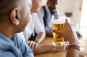 leisure and drinks concept - male friends drinking beer at bar or pub poster