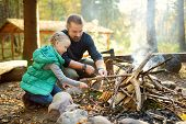 Cute Young Girl Learning To Start A Bonfire. Father Teaching Her Daughter To Make A Fire. Child Havi poster