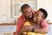 Mature black couple embracing on sofa while looking to each other. Romantic black man embracing woma poster