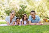 family, leisure and people concept - happy mother, father and two daughters laying on picnic blanket poster