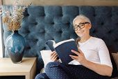 Smiling Senior Woman With Grey Hair In Eyeglasses Laying On The Bed And Reading Book In Bedroom poster