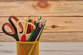 Colored Pencils And Scissors In Basket. Wood Color Pencils In Yellow Metal Pencil Holder. Stationery poster