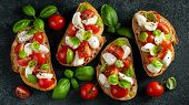 Bruschetta With Tomatoes, Mozzarella Cheese And Basil On A Cutting Board. Traditional Italian Appeti poster