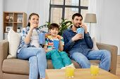 family, leisure and people concept - happy mother, father and son eating popcorn and watching tv at  poster