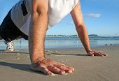 picture of personal trainer  - Man working out doing pushups on the beach in the early morning sun - JPG