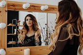 Beautiful Young Woman Looking At Her Reflection In A Dressing Room Mirror. Happy Glamorous Woman poster