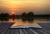 foto of ethereal  - Creative concept of beautiful simple image of sunset through tress reflected in lake in foreground coming out of magical book laid open - JPG
